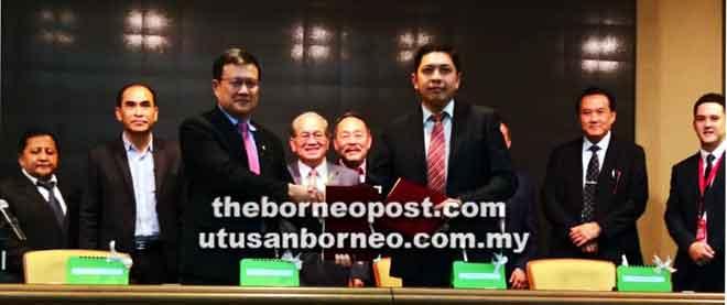 Uggah (tengah) menyaksikan Alvin (tiga kiri) dan Jeremy (tiga kanan) bertukar MoU.
