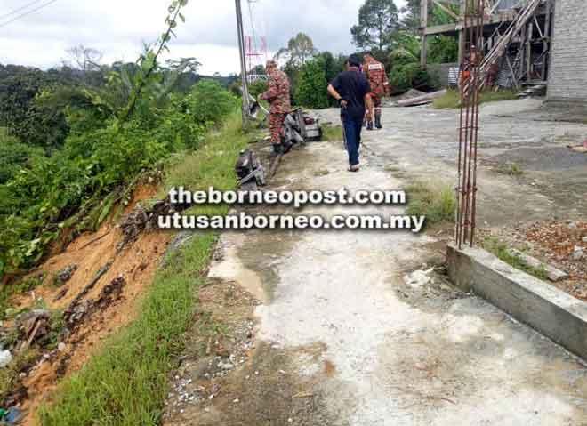 Anggota bomba memantau keadaan runtuhan tanah di lereng bukit Rumah Stanley Ejau, Jungkal dekat Betong semalam.