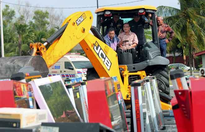 Wan Rosdy (duduk) menggunakan jengkaut untuk memusnahkan beberapa mesin perjudian sebagai simbolik pelupusan mesin simulator perjudian di pekarangan bangunan Majlis Perbandaran Kuantan (MPK), semalam. — Gambar Bernama