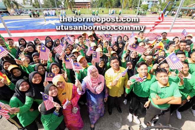 Affida (tiga kiri) merakamkan kenangan bersama warga SMK Tun Abang Haji Openg selepas berjaya membentuk Jalur Gemilang gergasi menggunakan 9,800 keping dulang telur terpakai. — Gambar Chimon Upon