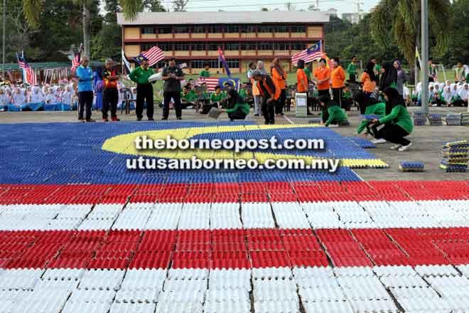 Pelajar SMK Tun Abang Haji Openg menyusun kepingan dulang telur terpakai bagi membentuk Jalur Gemilang gergasi. — Gambar Chimon Upon
