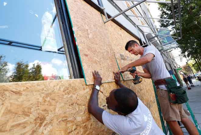 Pekerja kelihatan sedang bekerja untuk mengukuhkan papan lapis sebelum ketibaan Taufan Florence di Wilmington, Carolina Utara, Amerika Syarikat, kelmarin. — Gambar Reuters