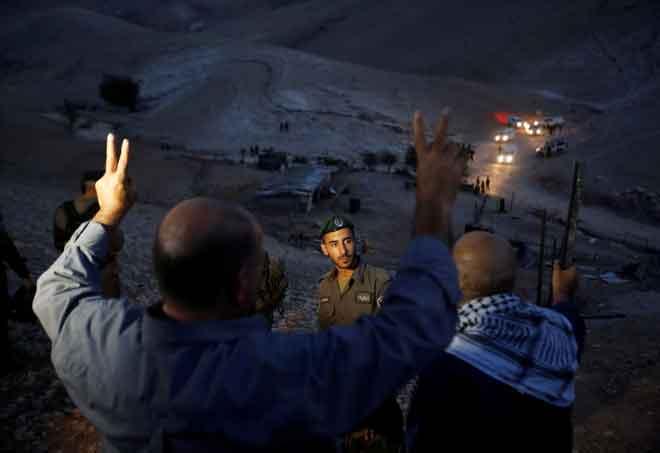 Penduduk Palestin menunjuk perasaan di hadapan tentera Israel selepas pasukan tentera mengalih teratak yang didirikan oleh aktivis Palestin untuk membantah rancangan Israel memusnahkan perkampungan Badwi Palestin, Khan al-Ahmar, di Tebing Barat semalam. — Gambar Reuters