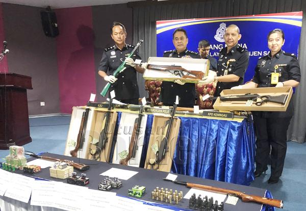 OMAR (dua kiri) menunjukkan senapang yang dirampas dari premis perniagaan yang diusahakan suspek.