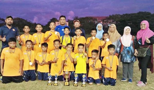 PEMAIN SK Tempasuk 1 dari Kota Belud bersama jurulatih dan guru meraikan kejayaan menjuarai Pertandingan Bola Sepak Jemputan Majlis Sukan Labuan Bawah 11 Tahun di Kompleks Sukan Labuan, Ahad lalu.