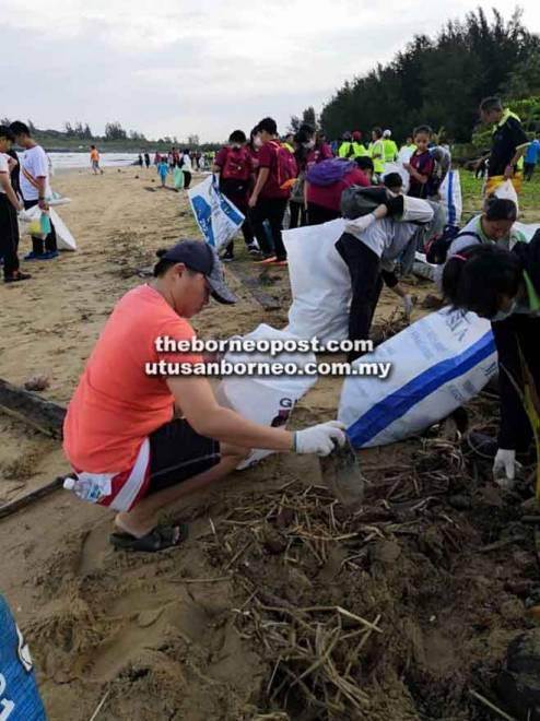 Peserta bersama-sama mengutip sampah di pantai Marina Bay pagi semalam.