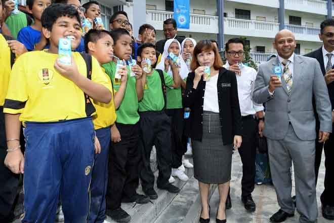 Teo (tiga kanan) bersama Pengarah Urusan Dutch Lady Malaysia Tarang Gupta (kanan) minum bersama pelajar Sekolah Kebangsaan Seri Bonus selepas merasmikan Majlis Sambutan Hari Susu Sekolah Sedunia 2018 dan Sumbangan Susu kepada Murid-murid Sekolah Rendah, Projek Perumahan Rakyat (PPR) Kuala Lumpur di Sekolah Kebangsaan Seri Bonus dekat Kuala Lumpur, semalam. — Gambar Bernama