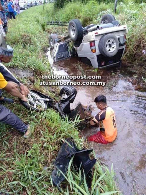 Penduduk kampung mengangkat naik motosikal mangsa dari dalam parit.