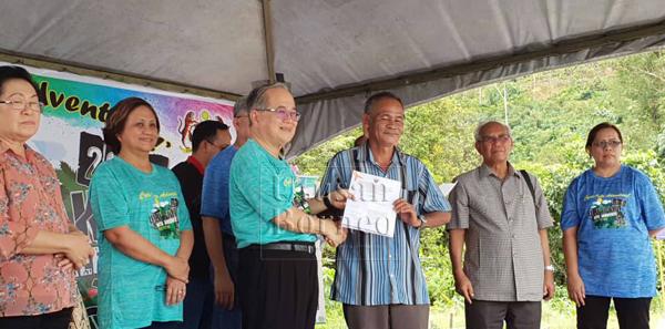 Uggah (tiga kiri) menyampaikan geran RTP kepada salah seorang pemimpin masyarakat di Betong sambil disaksikan yang lain.