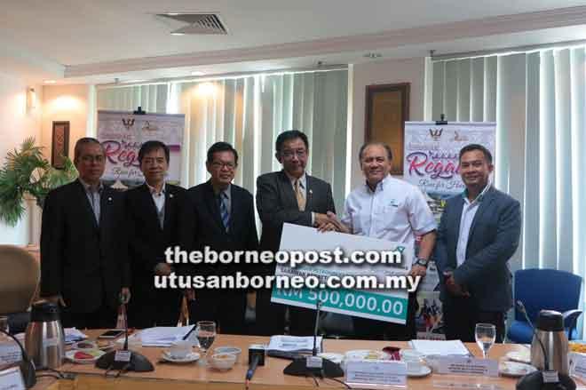 Karim menerima replika cek berjumlah RM500,000 daripada Pengurus Besar Petronas Wilayah Sarawak Shamsur Taha.