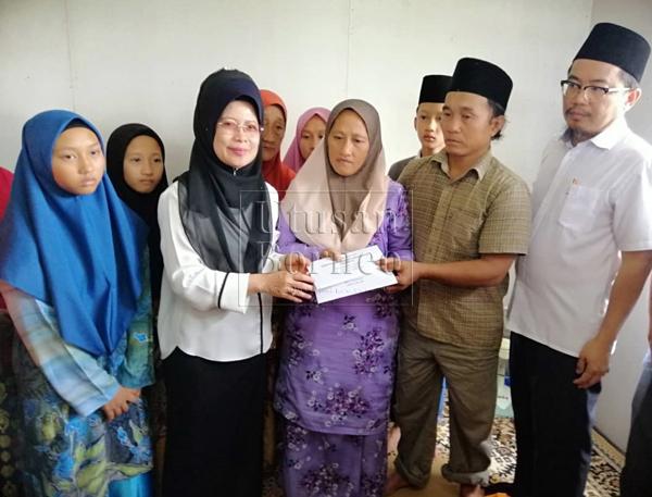 Fatimah menyampaikan sumbangan kepada ibu bapa Yahya, Halimah Geronggong dan Ali Bengang sambil disaksikan Juanda (kanan) serta ahli keluarga yang lain.