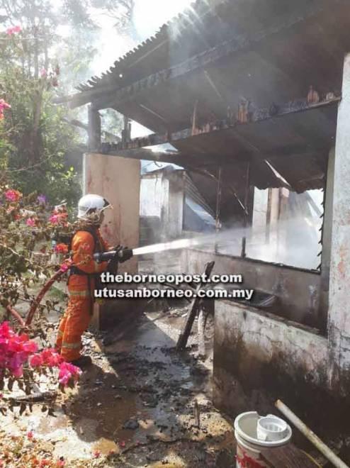 Anggota bomba berusaha memadam kebakaran yang memusnahkan rumah dua tingkat di Kampung Batu Mulung, Lawas Damit petang semalam.