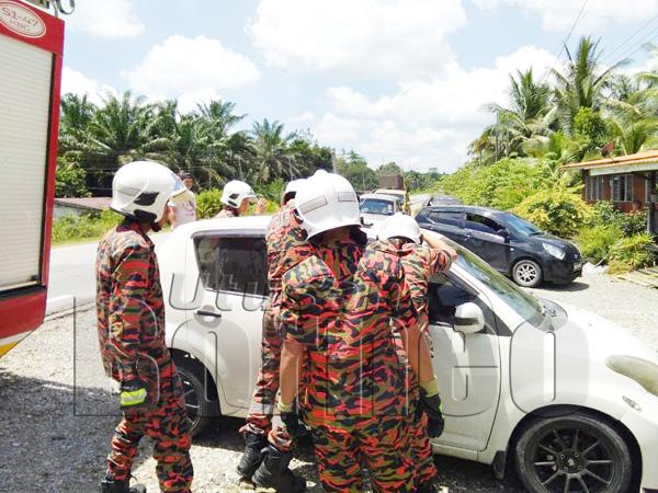 ANGGOTA bomba membuka pintu kereta terbabit bagi mengeluarkan kedua-dua mangsa.