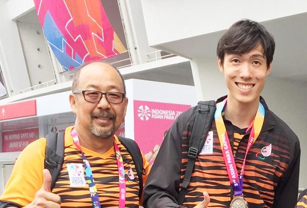 JONATHAN (kanan) bersama jurulatihnya, Yee Kok Wai selepas majlis penyampaian hadiah pada Sukan Para Asia di Jakarta Indonesia.
