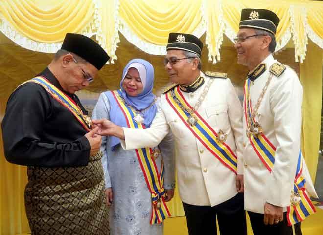 Mohd Redzuan (dua kanan) melihat Darjah Gemilang Seri Melaka yang diterima oleh Saifuddin selepas Istiadat Penganugerahan Darjah, Bintang dan Pingat Kebesaran Negeri Melaka sempena Sambutan Ulang Tahun Yang di-Pertua ke-80 di Seri Negeri Ayer Keroh. — Gambar Bernama