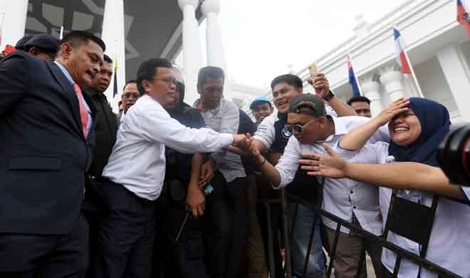 Mohd Shafie bersalaman dengan penyokongnya selepas diumumkan sebagai Ketua Menteri Sabah yang sah oleh Mahkamah Tinggi Kota Kinabalu, semalam. — Gambar Bernama