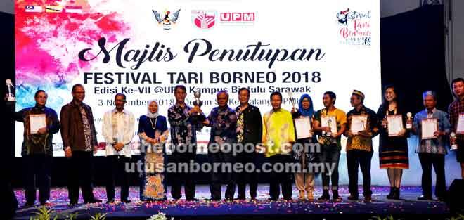 Sharkawi (lima kiri) menyampaikan piala pusingan juara Festival Tari Borneo Edisi Ke-7 2018 kepada wakil pengurusan UNTAN sambil disaksikan Dr Aini, Dr Mohd Roslan (empat dan tiga kiri), Dr Bujang, Hussaini (lapan dan tujuh kanan) serta pemenang-pemenang dari universiti, universitas dan kolej lain.