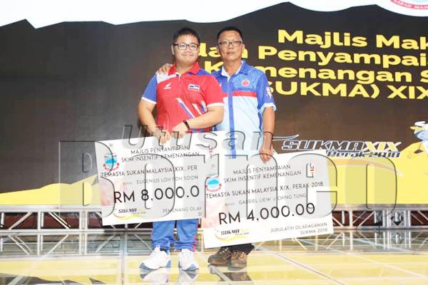 MEMBANGGAKAN, atlet memanah Sabah Eugenius (kiri) penerima insentif tertinggi dengan kejayaan merangkul empat emas dan dua perak juga dinobatkan sebagai Olahragawan SUKMA XIX Perak 2018. Bersamanya adalah jurulatihnya, Gabriel.