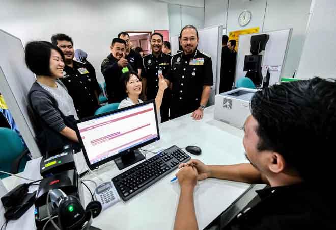 Mustafar (kanan) beramah mesra bersama orang awam sewaktu meninjau ruang kerja pejabat ketika merasmikan Pejabat Imigresen Cameron Highlands semalam. — Gambar Bernama