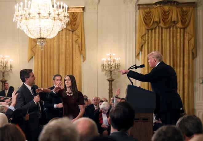 Seorang anggota kakitangan Rumah Putih cuba mengambil mikrofon yang dipegang oleh Acosta ketika beliau menyoal Trump pada satu sidang akhbar ekoran pilihan raya pertengahan penggal Kongres AS pada Selasa lepas di Washington, AS kelmarin. — Gambar Reuters