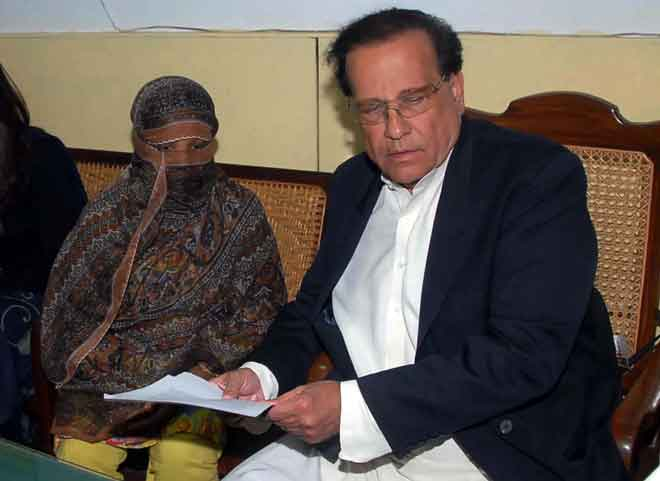 Gambar fail yang dirakam pada 20 November 2010 ini dan dikeluarkan oleh                      Rumah Gabenor Punjab menunjukkan Taseer (kanan) menyerahkan dokumen kepada Asia Bibi  di Penjara Pusat di Sheikhupura. — Gambar AFP