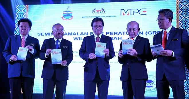 Shafie (tengah) menunjukkan buku garis panduan permohonan lesen berniaga selepas perasmian seminar Amalan Baik Peraturan (GRP) Wilayah Sabah semalam. — Gambar Bernama