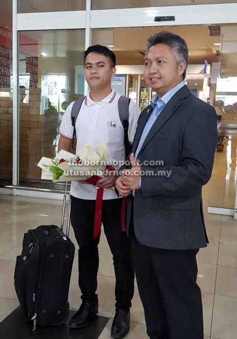 Franklin (kiri) disambut Snowdan semasa tiba di balai ketibaan antarabangsa LTAK di Kuching, semalam.