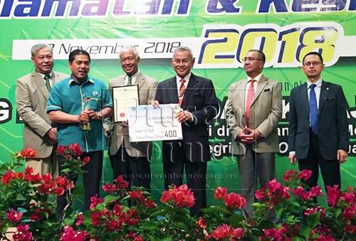 Talib menyampaikan anugerah kepada salah seprang penerima pada majlis perasmian Hari Integriti dan Inovasi serta Hari Keselamatan dan Kesihatan Pekerjaan DBKU 2018 di Kuching, hari ini.