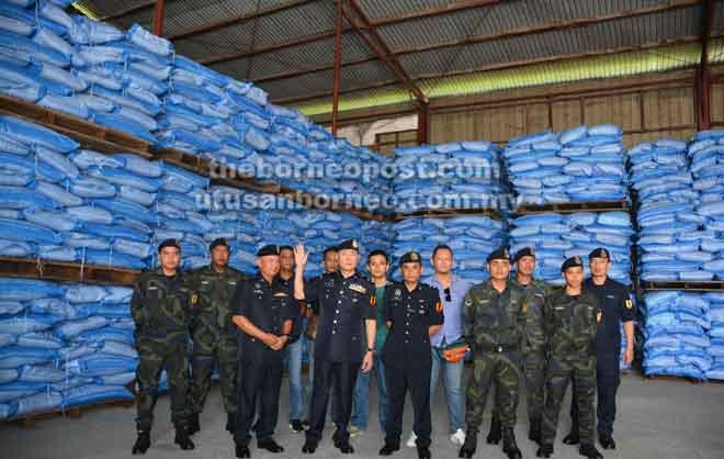 Tan (depan, dua kiri) bersama pasukan risikan dan serbuan semasa mengadakan sidang media di lokasi serbuan di Estet Perindustrian Piasau, Miri semalam.