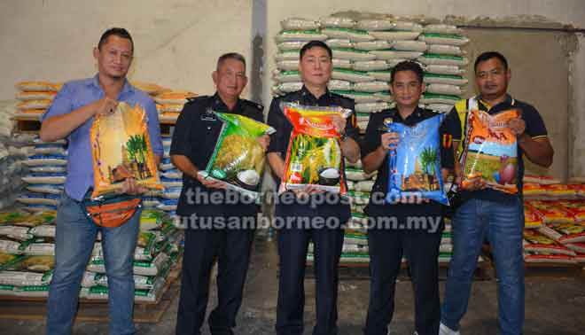 Tan (tengah) dan Rizuan (dua kanan) serta anggota menunjukkan beras seludup yang telah dibungkus semula menggunakan bungkusan tempatan.