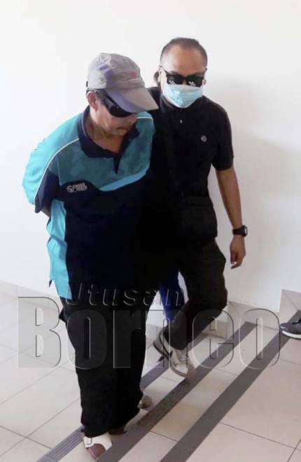 AMIR (kiri) diiringi anggota polis selepas selesai prosiding.