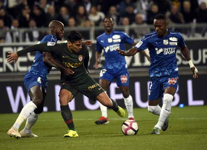 Falcao (duak kiri)diasak oleh dua pemain pertahanan Amiens ketika bersaing pada perlawanan Ligue 1 Perancis di Stadium Licorne, Amiens Selasa lepas. — Gambar AFP