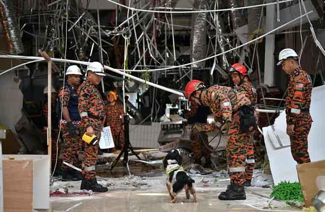 Anggota Bomba dan Penyelamat Sarawak membawa anjing pengesan ke tempat kejadian untuk memastikan tiada lagi mangsa tertimbus. — Gambar Bernama