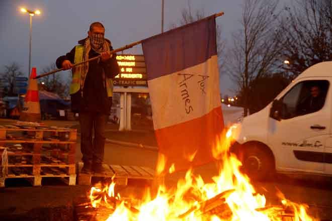 Seorang penunjuk perasaan yang memakai ves kuning, simbol protes pemandu Perancis yang menentang kenaikan harga diesel, membawa bendera dekat puing terbakar di jalan menuju ke A2 Paris-Brussels Motorway, di Fontaine-Notre-Dame, Perancis, kelmarin. — Gambar Reuters