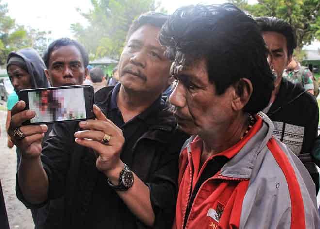 Gambar ini yang diambil kelmarin menunjukkan anggota keluarga mangsa pembunuhan di Nduga mempamerkan gambar dalam telefon pintar mereka yang menunjukkan salah seorang mangsa, di Wamena, wilayah Papua. — Gambar AFP