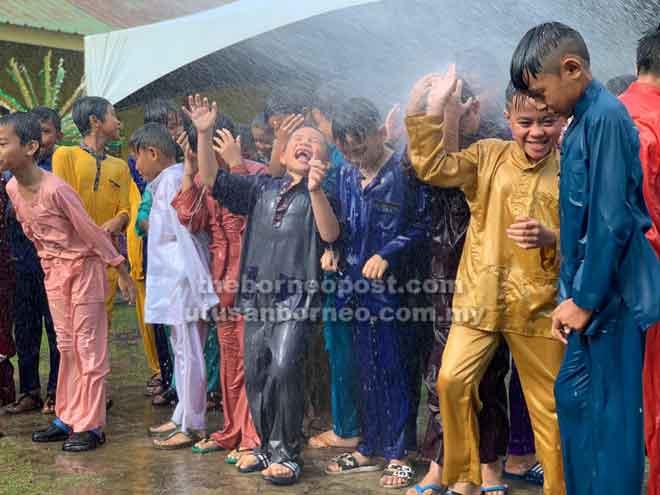 Kanak-kanak menikmati saat-saat disiram air sebelum bermulanya acara berkhatan di Miri, baru-baru ini.