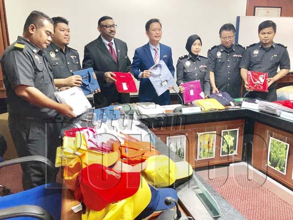 GEORGIA (tengah) bersama pegawai KPDNHEP lain menunjukkan hasil rampasan barangan tiruan semasa sidang media pada Khamis.