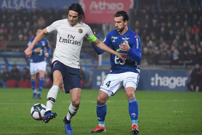 Cavani (kiri) cuba melepasi kawalan ketat pemain pertahanan Strasbourg ketika bersaing pada perlawanan liga di Stade de la Meinau, Strasbourg Rabu  lepas. — Gambar AFP