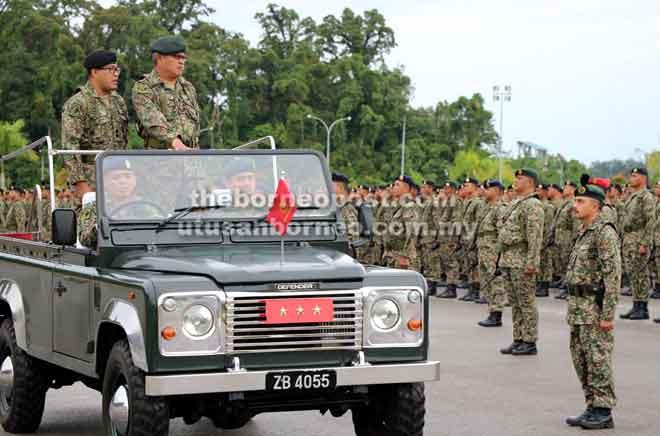 Zamrose (dua kiri) menaiki kenderaan khas memeriksa perbarisan sempena Majlis Perintah Ulung Panglima Medan Timur Tentera Darat di Kem Muara Tuang semalam.