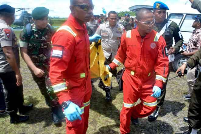 Mayat pekerja pembinaan, dibunuh oleh kumpulan pemisah, dilihat diusung dari helikopter tentera di Lapangan Terbang Mozes Kilangin Timika di Papua semalam. — Gambar AFP