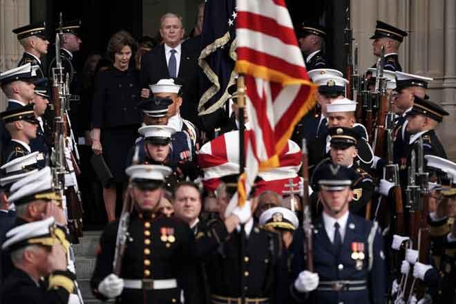 Bush dan isterinya Laura menyertai pengawal kehormat yang mengusung keranda bapanya, H.W. Bush,            ke kereta mayat yang menunggu di luar selepas upacara pengebumian rasmi di Katedral Nasional di Washington kelmarin. — Gambar AFP