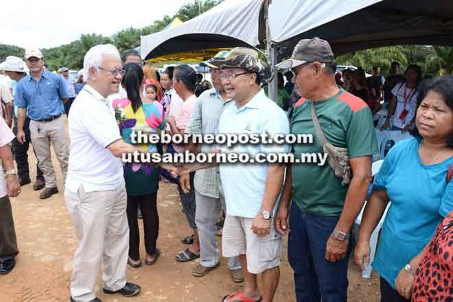APA KHABAR?: Abdul Hamed (kiri) bersalaman dengan hadirin ketika menunggu ketibaan Dr Rundi ke ladang kelapa sawit di Ulu Sebauh, Bintulu.
