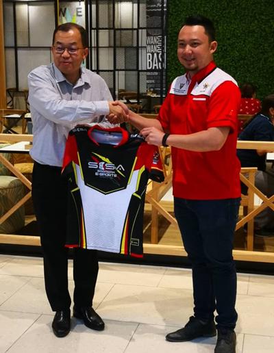 Stephen (kiri) menyerahkan jersi acara E-Sport anjuran CityONE, yang pertama kali dianjurkan di Sarawak kepada Presiden Persatuan E-Sport Sarawak, Afiq Fadhli Narawi (kanan) sempena Upacara Pembukaan Semula CityONE di sini, hari ini.