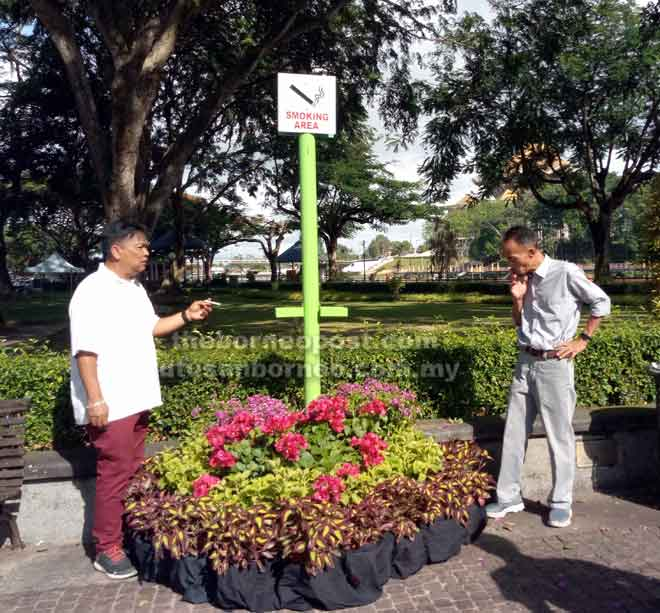 Safani (kiri) dan Zulkepli merokok secara berhemah di salah satu lokasi khas yang ditetapkan DBKU di Tebingan Kuching.