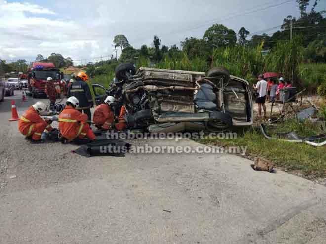 Anggota bomba berusaha mengeluarkan mangsa yang tersepit dalam kereta.