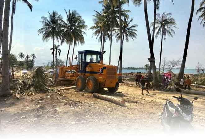 Sebuah jentera digunakan untuk membersihkan laluan ekoran laluan di kecamatan (Sumur) dihalang oleh pokok tumbang, batu-bata serta lumpur yang dibawa oleh arus tsunami dari laut. — Gambar Bernama