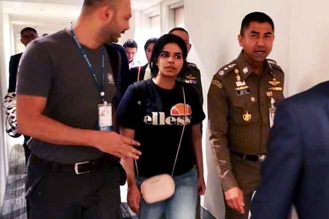 Gambar serahan ini yang diambil dan dikeluarkan oleh Biro Imigresen Thailand pada 7 Januari lepas menunjukkan Qunun (tengah) diiringi seorang pegawai imigresen Thai (kanan) dan pegawai UNHCR di Lapangan Terbang Antarabangsa Suvarnabhumi di Bangkok, Thailand. — Gambar AFP