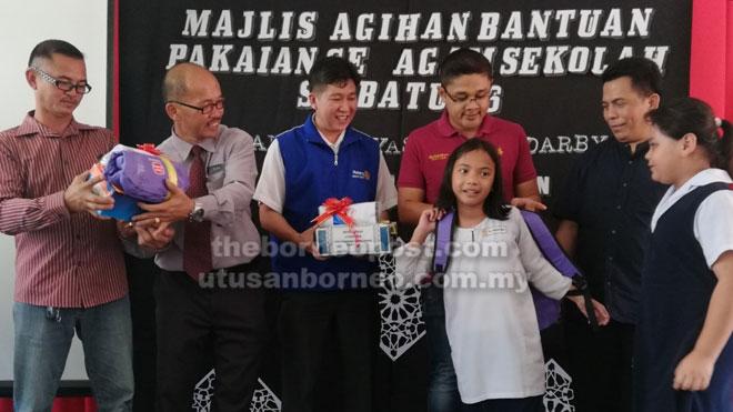 Irwan (dua kanan) melakukan simbolik penyerahan bantuan kepada salah seorang murid SK Batu 36, Selangau diperhatikan Alas (dua kiri), Jong (tengah) dan tetamu.