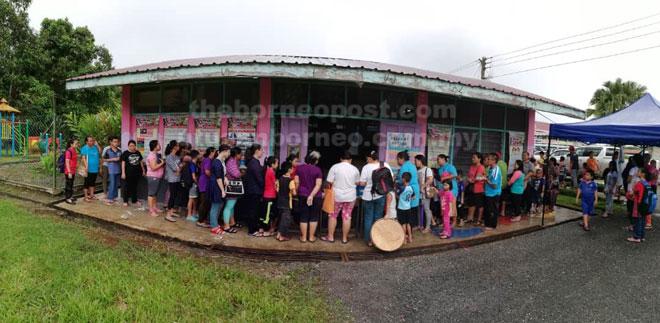 Ibu bapa yang hadir mendaftar membolehkan untuk anak-anak menerima sumbangan bantuan pakaian seragam sekolah.