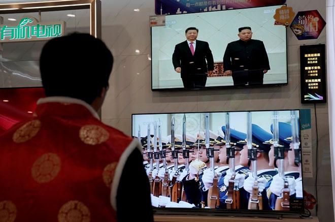 Skrin televisyen menunjukkan rakaman media kerajaan China CCTV bagi pertemuan Kim dengan Xi, di sebuah kedai elektronik di Beijing, China pada Khamis. — Gambar Reuters